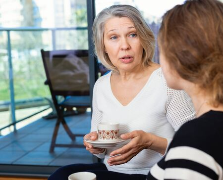 Happy senior woman enjoying conversation with young girl over cup of coffee at home Foto de archivo - 135413995