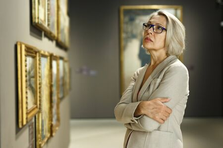 Portrait of thoughtful elderly woman exploring art pieces in art gallery
