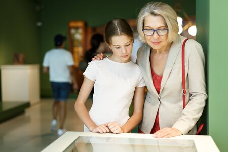 Teenage girl and mature woman observing exhibition