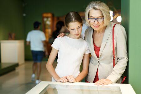 Teenager-Mädchen und reife Frau, die Ausstellung beobachten