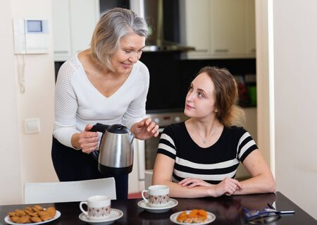Smiling elderly woman pouring coffee to her young female guest at home Foto de archivo - 135416564