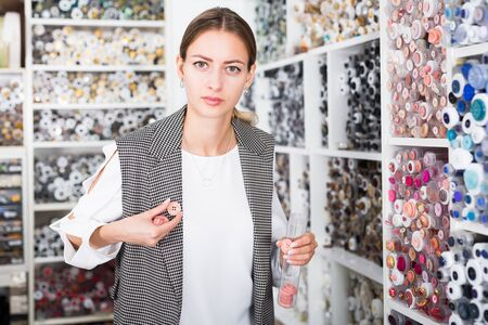 Portrait of young attractive woman choosing buttons for clothes in needlecraft store