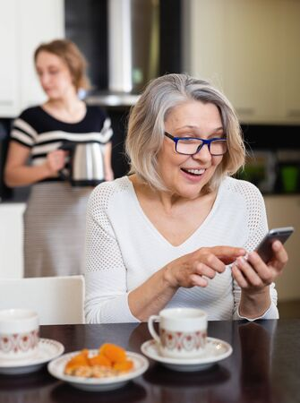 Positive senior woman using phone while young woman making tea