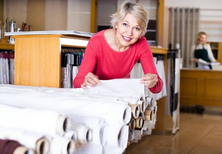 aged female customer looking for beautiful fabric in home textile shop Stok Fotoğraf