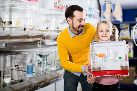 young european father and daughter enjoying their purchase of canary bird in pet shop Stock fotó