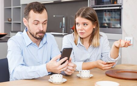 Young discontented couple sitting with phones in kitchen interior, finding out relationship 免版税图像