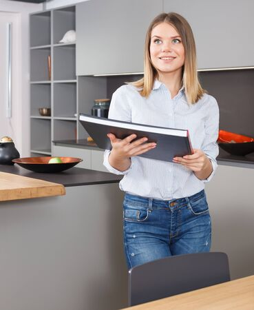 Portrait of smiling attractive girl holding book while standing in stylish interior of home kitchen Banque d'images - 135490928