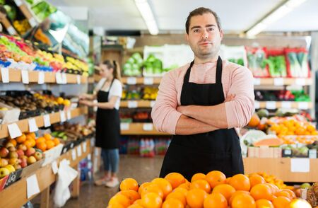 Young man in apron selling fresh oranges and fruits on the supermarket