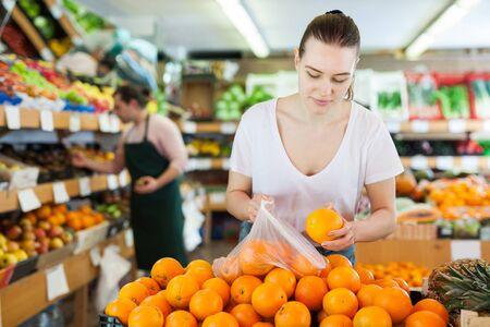 Cliente della giovane donna che sceglie le arance fresche sul supermercato