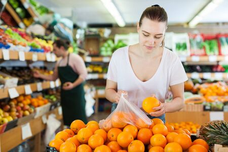 Junge Kundin, die frische Orangen im Supermarkt wählt