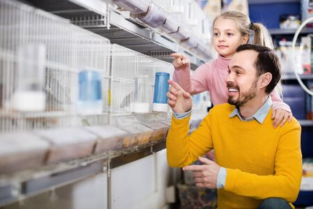 Smiling father and girl deciding on best bird to keep in pet shop Stock fotó