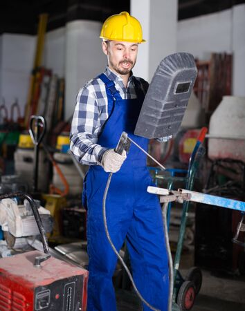 Male worker is starting to work with welding machine at workshop.