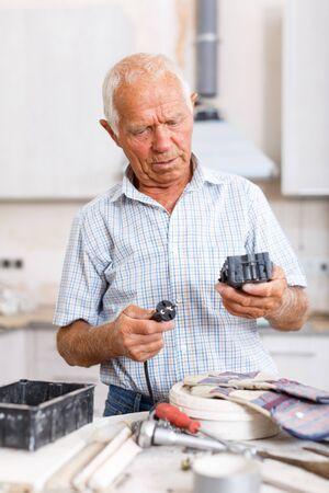 Abile uomo anziano impegnato in lavori di ristrutturazione al chiuso