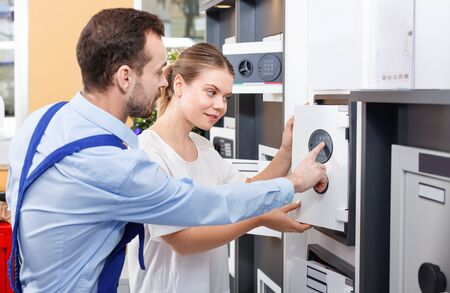 Attractive cheerful girl consulting about purchase of home safe with worker in specialty workshop Stock Photo