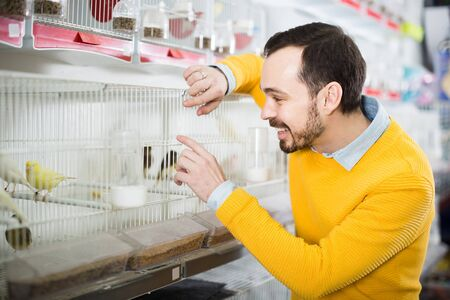 Young russian male customer deciding on best bird to keep in pet shop