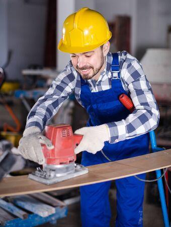 Adult is using grinder for construction work at workshop. Banque d'images - 135490816