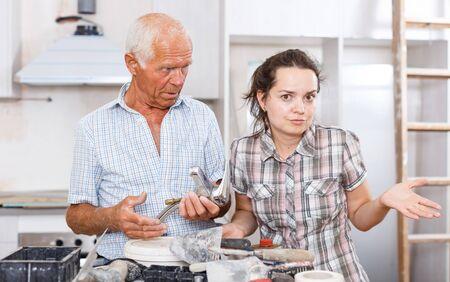 Mujer joven perpleja y hombre mayor tratando de averiguar cómo instalar el grifo mezclador durante la revisión en casa Foto de archivo