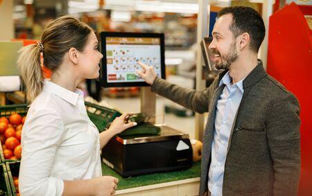 La coppia felice è in piedi con frutta fresca vicino alla pesatrice al supermercato