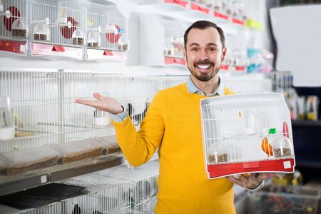 Young smiling man enjoying his purchase of canary bird in pet shop Stock fotó