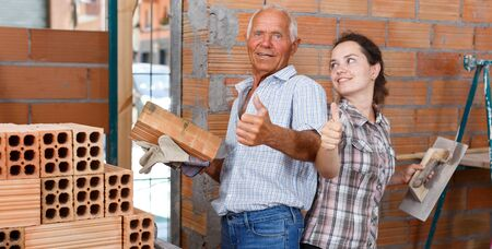 Portrait of cheerful woman with her smiling elderly father during overhaul at their home