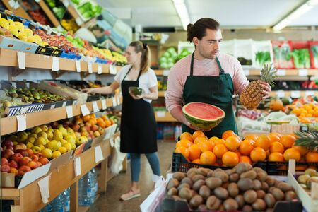 Adult man and woman wearing aprons offering fresh fruits on the supermarket