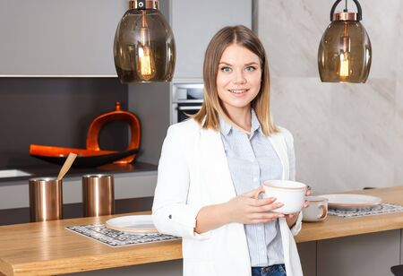 Portrait of stylish young woman with cup of tea in modern home kitchen Banque d'images - 135490756