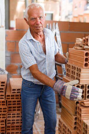 Anciano hábil inspección de ladrillos para instalar la pared en un edificio en construcción Foto de archivo