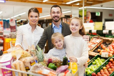 portrait of positive family is standing with trolley with food for dinner in the supermarket. Reklamní fotografie - 135494675