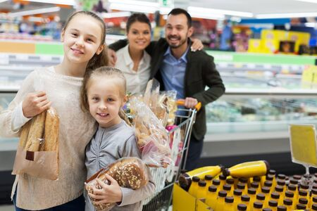 Smiling family of four is standing with purchases in the grocery Reklamní fotografie - 135494715