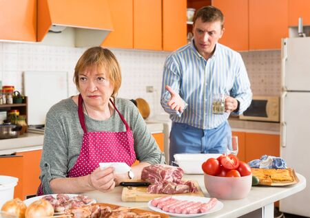 Upset elderly woman preparing dinner in home kitchen on background with disgruntled son berating her