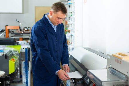 Service man uses plotter in printing shop