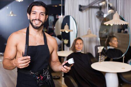 portrait of smiling man hairdresser and woman visitor in salon Standard-Bild