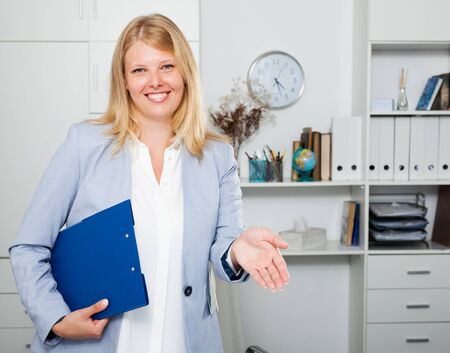Adult smiling blond woman in business suit standing in modern office and holding folder in hands Stock Photo