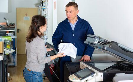 Office employee reports printer error to service engineer Stock Photo