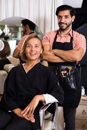 positive man makeup artist standing near client woman