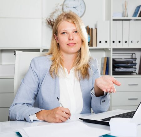 Positive lady business adviser sitting at workplace and gesturing with her hands Banco de Imagens