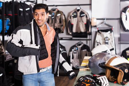 Adult man is trying up jacket-equipment in the moto shop