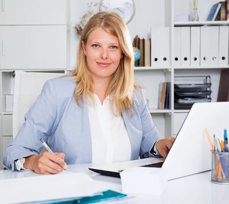 Positive female business consultant sitting at workplace in office Imagens