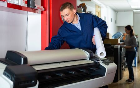 Worker loads new roll of paper into the plotter Stock Photo