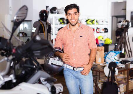 Porträt eines fröhlichen, positiven männlichen Kunden, der im Sportgeschäft in einem neuen Helm posiert. Standard-Bild