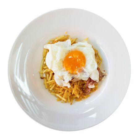 Popular Spanish dish Huevo cabreado of fried egg served with fried potatoes and sliced ham. Isolated over white background