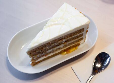 Slice of delicate carrot cake with light mascarpone cream and peach jam