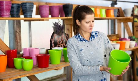 Young woman amateur gardener choosing pots for growing plants in floral and garden supplies store