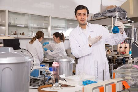 Nice male chemist working in laboratory, analyzing liquid samples in test flasks