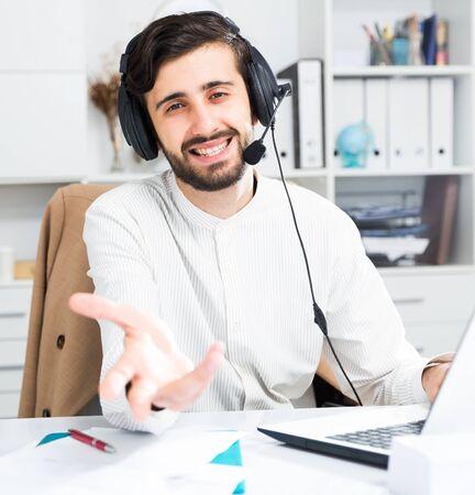 Positive man call center operator with headphones sitting at office table