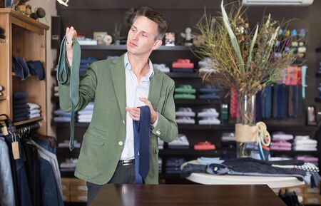 Young happy male customer examining a ties at male cloths store