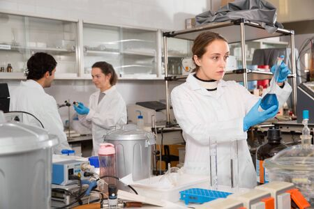 Diligent efficient positive  female lab technician working with reagents in test tubes during chemical experiment