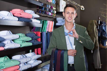 Positive man choosing new tie in male cloths store Reklamní fotografie