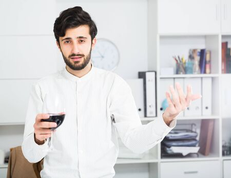 Handsome young office worker holding glass of red wine and gesturing at office