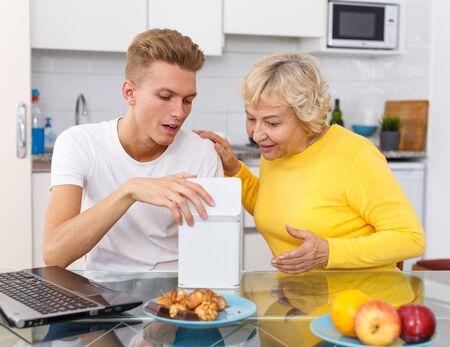 Reife Frau, die ihrem glücklichen erwachsenen Sohn ein Geschenk gibt - weiße Schachtel Standard-Bild